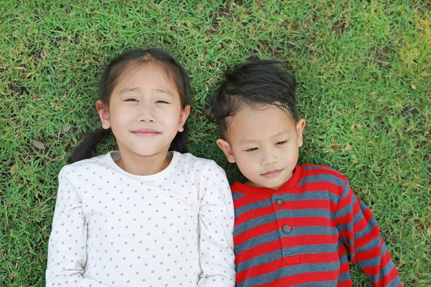 Asian little child boy and girl lying on green grass outdoors in summer park