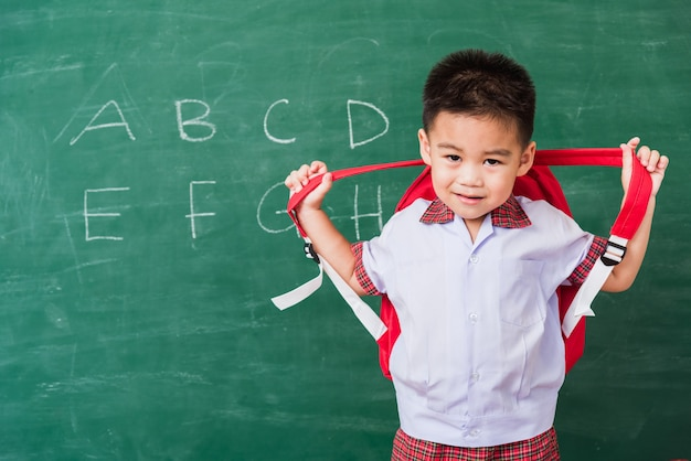黒板に笑みを浮かべてランドセルスタンドを身に着けている学生服のアジアの小さな子供男の子幼稚園幼稚園