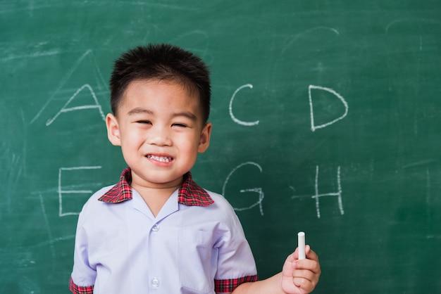 Asian little child boy kindergarten preschool smile in student uniform hold white chalk
