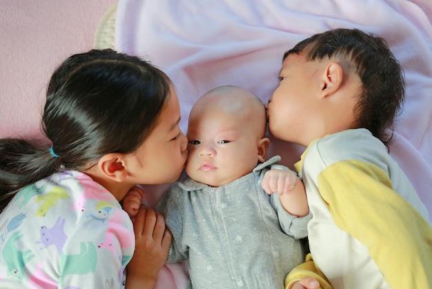 Азиатская маленькая девочка и ее младший брат целуют ее сестру, лежа на кровати