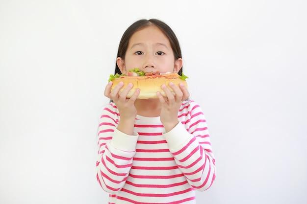 흰색 배경에 고립 된 뜨거운 개를 먹는 아시아 어린 아이 소녀