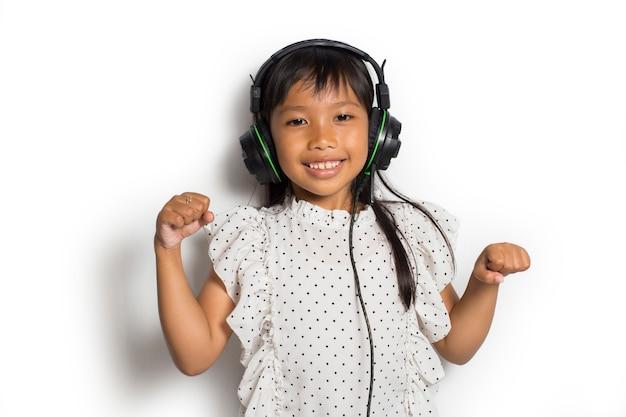 音楽を楽しんでいるアジアの小さな子供の女の子。真のポジティブな感情を表現するダンスと動き