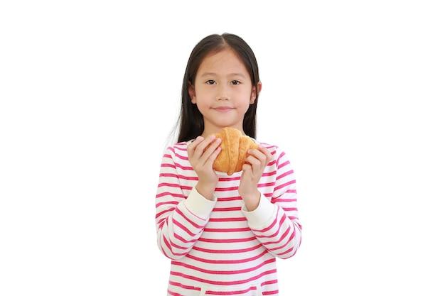 Азиатская маленькая девочка держит круассан на белом фоне