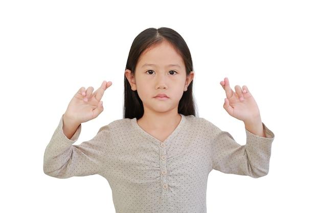 Азиатская маленькая девочка держит пальцы скрещенными на белом фоне