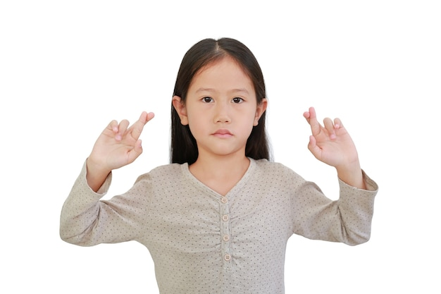 Asian little child girl holding fingers crossed isolated on white background