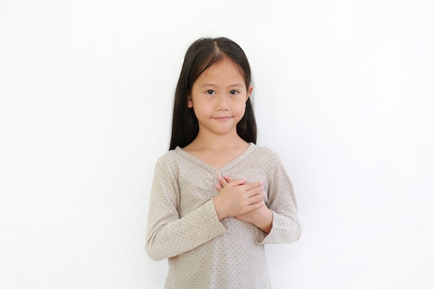 Asian little child girl holding hands on chest isolated on white background