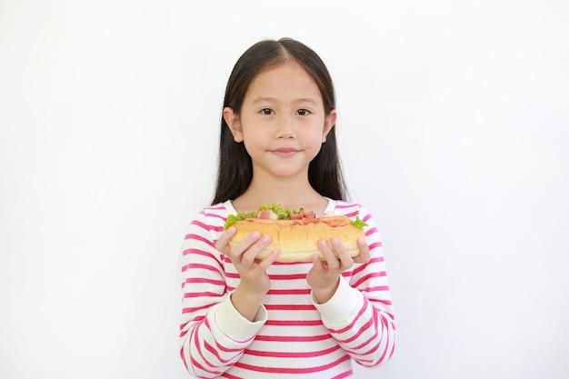 白い背景の上にあなたのためのホットドッグを保持しているアジアの小さな子供の女の子