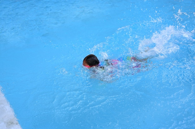 Asian little child girl learning to swim in pool. schoolgirl practicing to swimming.
