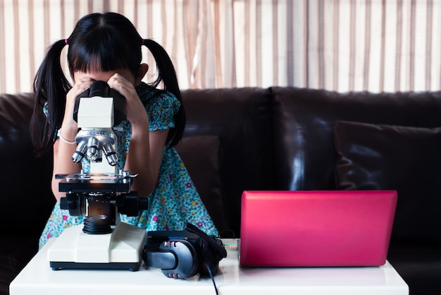 Asian little child  girl looking microscope and  learning online by using laptop and  at home , distance education