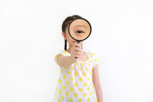 흰색 배경에 고립 된 돋보기를 통해 찾고 아시아 어린 아이 소녀. 손에 돋보기에 집중