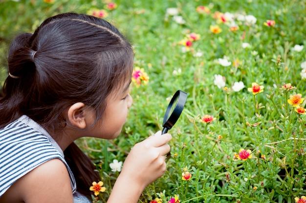 Азиатская девочка маленькая девочка, глядя через увеличительное стекло на красивый цветок в саду
