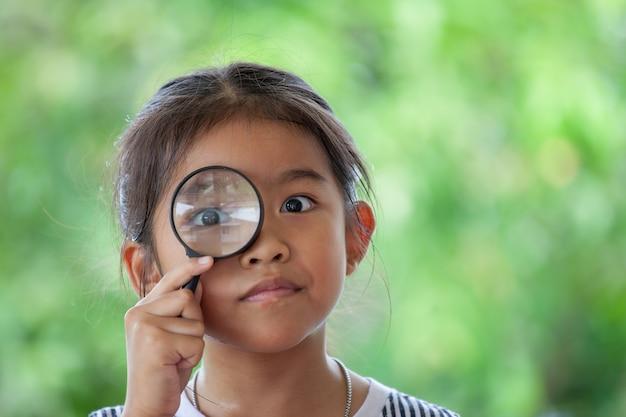 Азиатская девочка маленькая девочка, глядя через увеличительное стекло на фоне зеленой природы