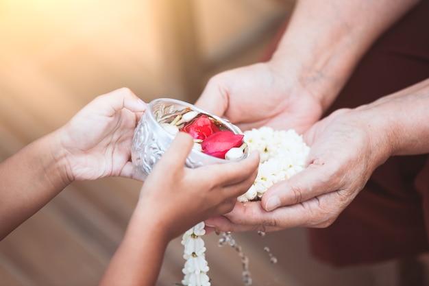 アジアの小さな子供の女の子が高齢の老人や敬虔な祖父母の手に水を注ぐ