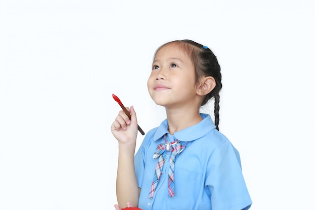 Asian little child girl in school uniform holding red dipped paintbrush thinking of drawing something .