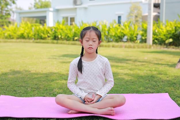 庭で瞑想に座っているアジアの小さな子供の女の子