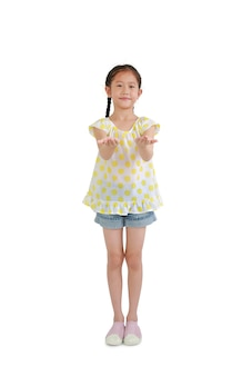 Азиатская маленькая девочка ребенка стоя с руками выражения для того чтобы получить и поддержать что-то изолированное на белой предпосылке. полная длина