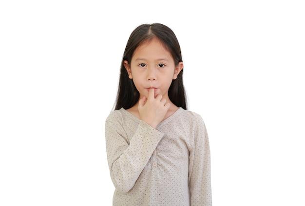흰색 배경에 고립 된 그의 입에 손가락을 빠는 아시아 어린 아이 소녀.
