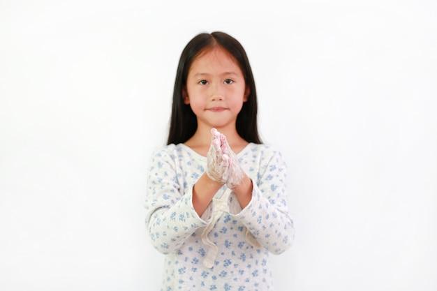 Азиатская маленькая девочка ребенка мытье рук с водой и мылом над белой предпосылкой. концепция профилактики гигиены и вирусных инфекций. сосредоточьтесь на руках