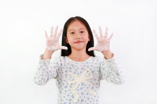 Азиатская маленькая девочка ребенка мытье рук с водой и мылом над белой предпосылкой. малыш показывает мыльные ладони. концепция профилактики гигиены и вирусных инфекций. сосредоточьтесь на руках