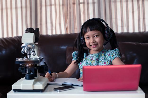 Наушники азиатской маленькой девочки нося учя онлайн с помощью компьтер-книжки и микроскопа дома, дистанционное обучение