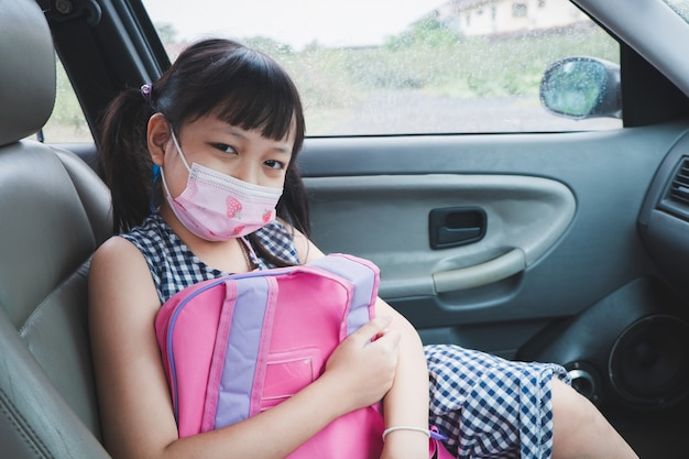 Asian little child girl wearing mask sitting in the car