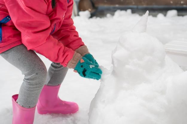 Азиатская девочка маленькая девочка в розовой куртке и зимней перчатке, играя со снегом и литье