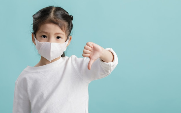 Asian little child girl wearing respirator mask for stop coronavirus outbreak, new virus covid-19 from wuhan china concept, empty space isolated on blue long banner