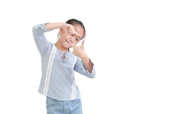 白い壁に分離された指でフレームを作るアジアの小さな子供