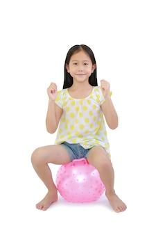 クリッピング パスと白い背景に分離された円形のシリコーンの膨脹可能なピンクのこぶのボールの上に座って、アジアの小さな子供に乗る