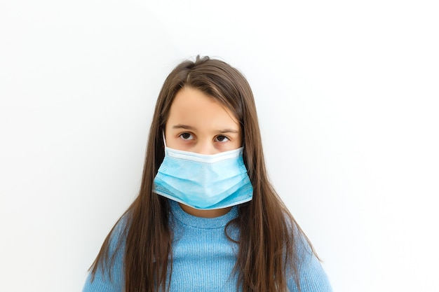 Asian little chinese girl wearing a protective mask in isolated white background.