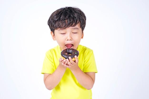 흰색 절연 큰 도넛을 먹는 아시아 작은 귀여운 소년