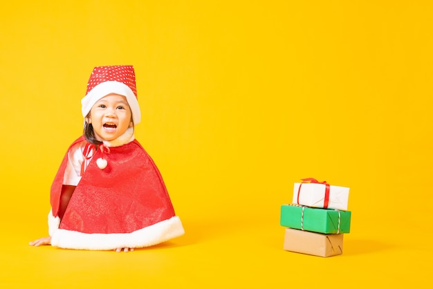 Asian little cute child girl smile in red santa claus hat the concept of holiday christmas xmas day