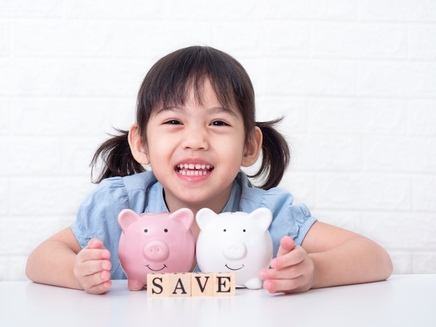 Asian little cute girl 4 years old saving money in to a pink pig on white wall
