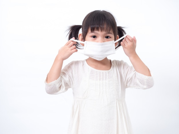 Asian little cute girl 4 years old wearing a hygienic face mask to protective spread the corona virus covid-19 cold flu or pollution on white wall