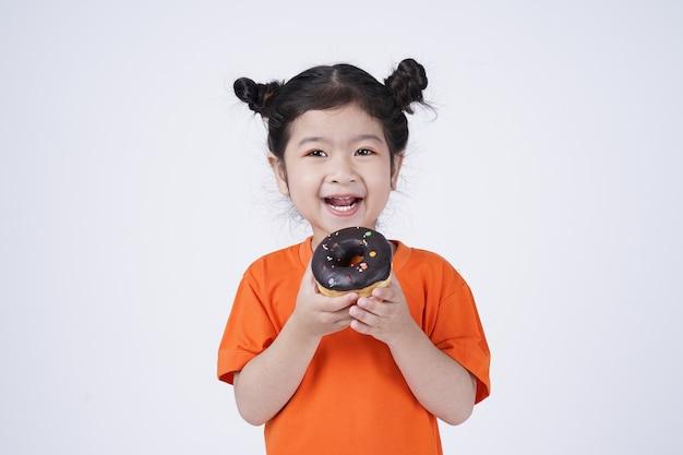 白で隔離の大きなドーナツを食べるアジアの小さなかわいい女の子