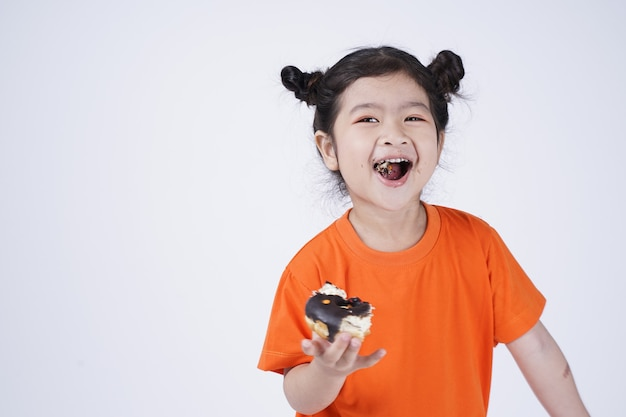 흰색 절연 큰 도넛을 먹는 아시아 귀여운 소녀