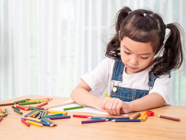 Asian little cute girl sitting and use color pencil drawing cartoon in white paper on wooden table.