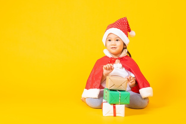 Asian little cute girl smile in red santa claus hat the concept of holiday christmas xmas day