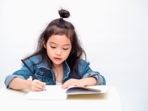 Asian little cute girl use color pencil and drawing cartoon on notebook.