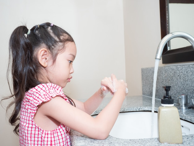 Asian little cute girl washing hands with soap at basin. child cleaning hands with soap to protect bacteria and coronavirus , covid-19