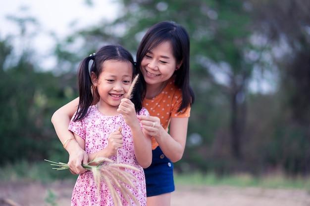 Азиатская маленькая дочка развлекается и счастлива со своей матерью