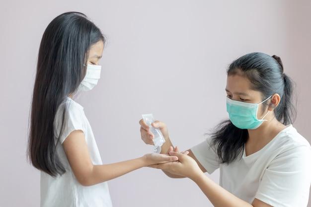 アジアの少女と女性は防護マスクを着用します。