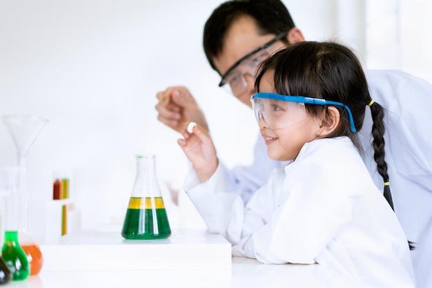 Азиатская маленькая девочка и учитель проводят эксперимент по разделению фаз нефти и воды.