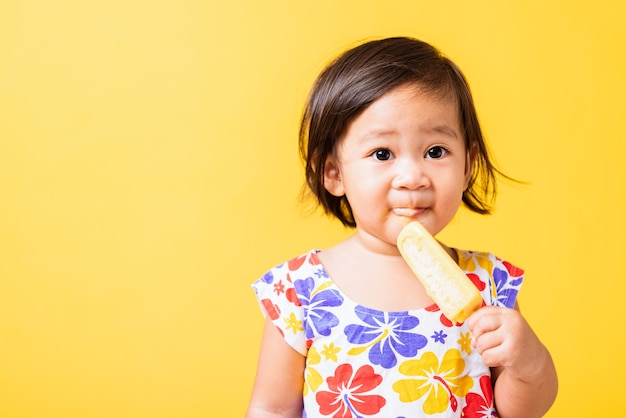 Asian little girl attractive laugh smile wearing dick pattern shirt holds and eating sweet wood