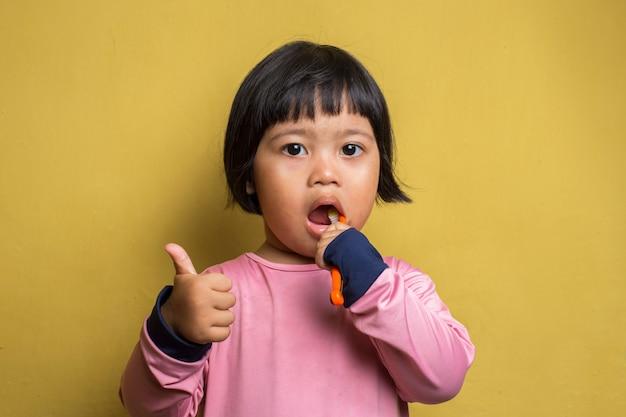 Asian little girl brush her teeth on yellow wall