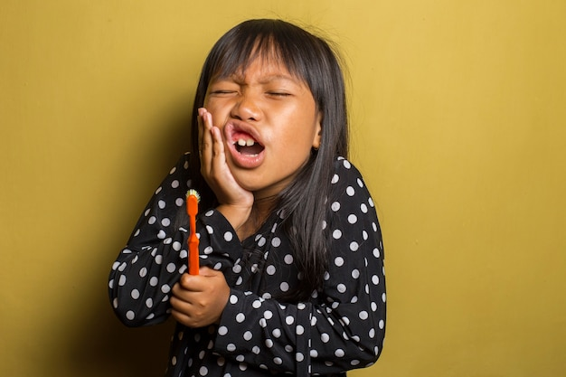 Asian little girl brushing her teeth