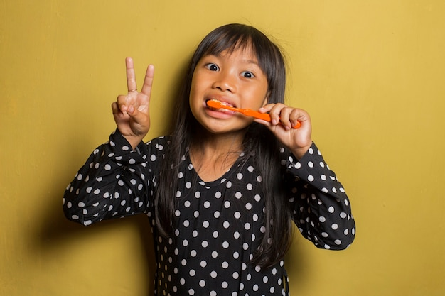Азиатская маленькая девочка, чистящая зубы