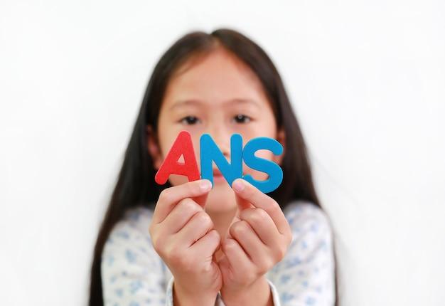 Азиатский ребенок маленькой девочки держа текст губки ans в руках над белой предпосылкой. концепция образования и развития. сосредоточьтесь на письмах в руке