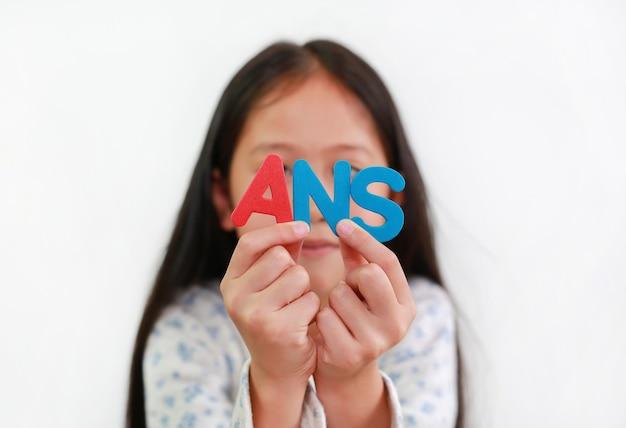 흰색 배경 위에 손에 ans 스폰지 텍스트를 들고 아시아 어린 소녀 아이. 교육 및 개발 개념입니다. 손에 있는 편지에 집중