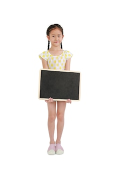 白い背景に分離された空白の黒板を保持しているアジアの小さな女の子。全長